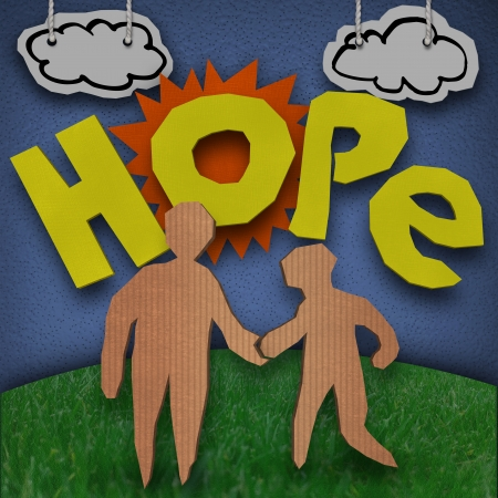 A paper and cardboard cutout diorama with the word Hope in front of the sun with clouds in the sky and two people - and adult and child - holding hands on grass 스톡 콘텐츠