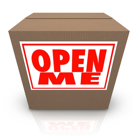 affixed: The words Open Me on a label affixed to a closed cardboard box, inviting you to open it up and see the mystery contents inside