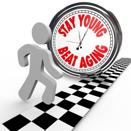 personas mayores: Un corredor en una carrera contra el tiempo cruza la línea de meta antes de que un reloj con las palabras Stay Young Envejecimiento golpe, un intento de mantener la juventud a través del ejercicio y poner en marcha el proceso de envejecimiento