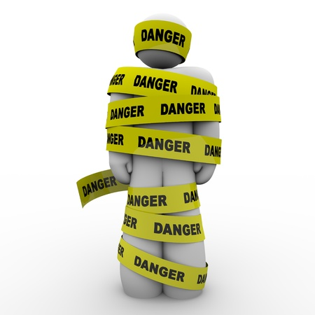 vulnerable: A person or man wrapped in yellow tape marked Danger, illustrating a warning, caution, hazard, crisis or emergency