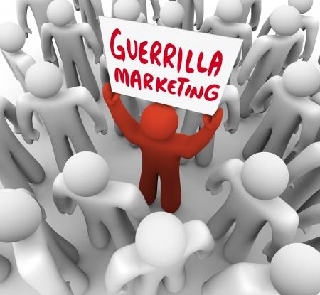 Die Worte Guerrilla Marketing auf einem Schild durch eine einzigartige Person in einer Menschenmenge hielt, ein Vermarkter Förderung sein Produkt oder seine Marke an Kunden in einem Publikum Standard-Bild