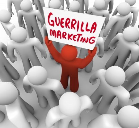 The words Guerrilla Marketing on a sign held by a unique person in a crowd, a marketer promoting his product or brand to customers in an audience photo