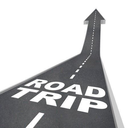 road ahead: The words Road Trip on a street of blacktop pavement representing a fun adventure you will experience when traveling in ground transportation to your destination
