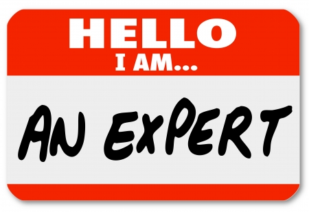 The words Hello I Am An Expert written on a red nametag or sticker photo