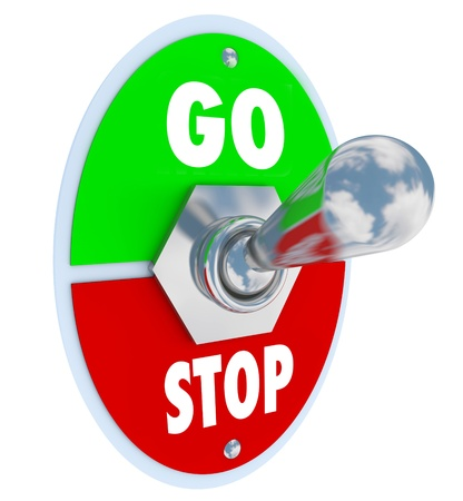 stopped: A metal toggle switch with plate reading Go and Stopped, turned into the up or on position to start a process or beginning a new chapter or event Stock Photo