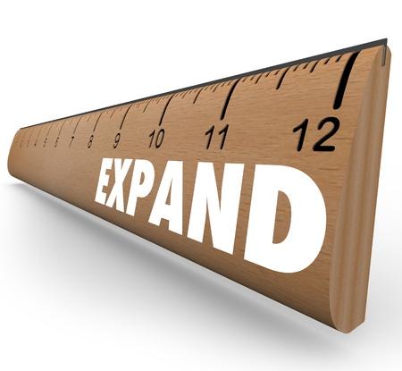 Een houten liniaal met het woord uitbreiden tot uitbreiding van het bedrijf of de groei van persoonlijk niveau of een andere kwaliteit symboliseren Stockfoto
