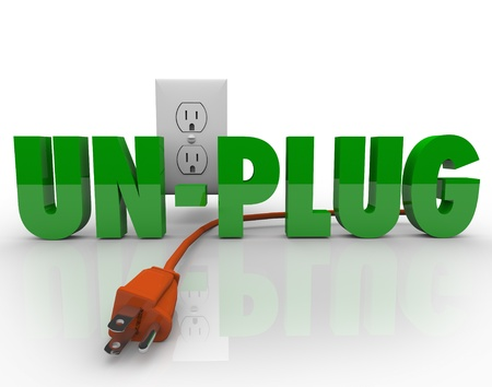 The word Unplug in green letters with an orange electrical cord disconnected from the power outlet photo