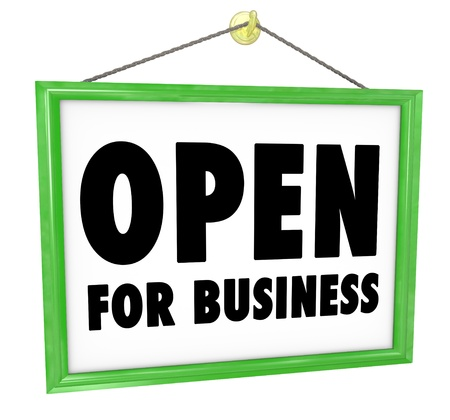 new start: The words Open for Business on a sign that would hang on the wall or in a window of a shop, store or business to invite customers inside for a grand opening or for regular business hours