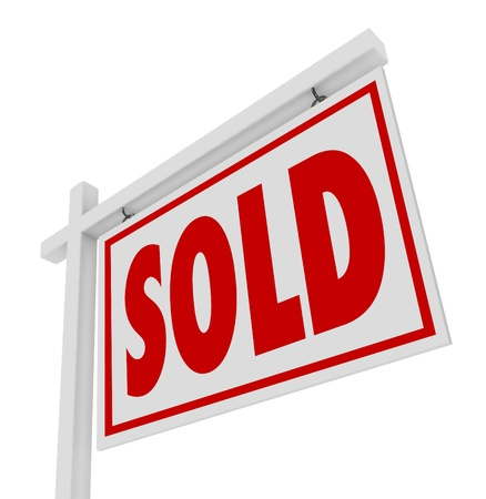 first house: A white real estate for sale sign with the word Sold representing a successfully closed home, house or property transaction Stock Photo