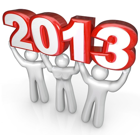 A team of people celebrate the new year holiday by lifting the number 2013 in a party or celebration photo