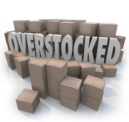 stockpile: The word Overstocked in the middle of a warehouse of cardboard boxes to symbolize an oversupply or surplus of merchandise on hand Stock Photo