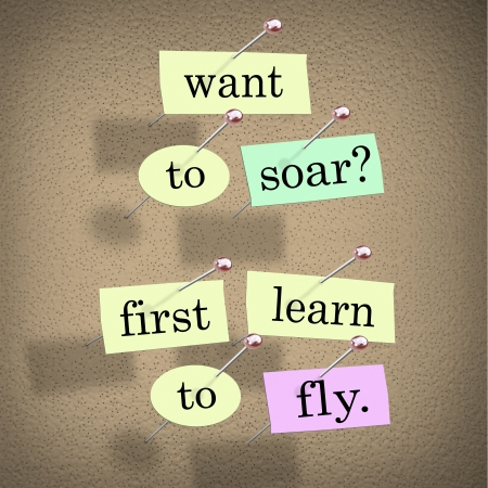 accomplishing: The saying Want to Soar, First Learn to Fly on pieces of paper pinned to a bulletin board, a motivational bit of advice to help you achieve success in life