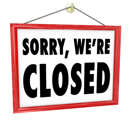 were: Sorry Were Closed sign hanging in a store window to represent closure, bankruptcy, after hours or going out of business
