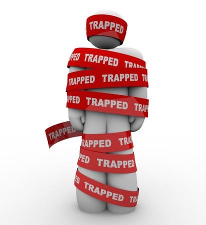 immobile: Una persona que est� envuelto en cinta roja con la palabra Atrapado como s�mbolo de ser atado, trangled o restringido por captores o reglas y regulaciones Foto de archivo