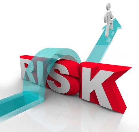 pitfall: A person jumps over the word Risk to symbolzine avoiding danger or hazards and being careful and prepared to overcome dangerous obstacles Stock Photo