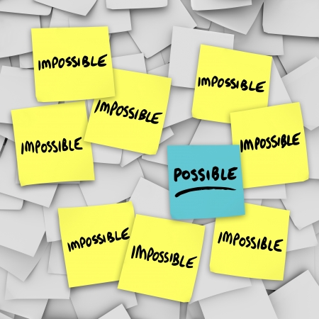 taking charge: The words Possible and Impossible on sticky notes to symbolize good positive attitude and thinking of opportunity
