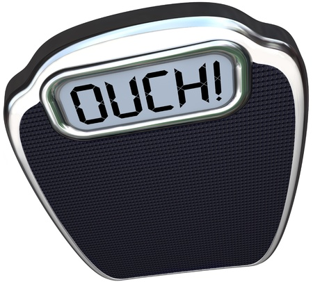 The word Ouch on a scale digital display representing pain from a heavy or obese person who needs to lose weight standing on it photo