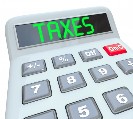 budgetary: A plastic calculator displays the word Taxes symbolizing the need to file annual tax returns Stock Photo