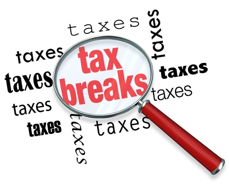 paying: A magnifying glass hovering over the word tax breaks, symbolizing the advice and tricks that an accountant can use to increase deductions and save money when filing tax returns