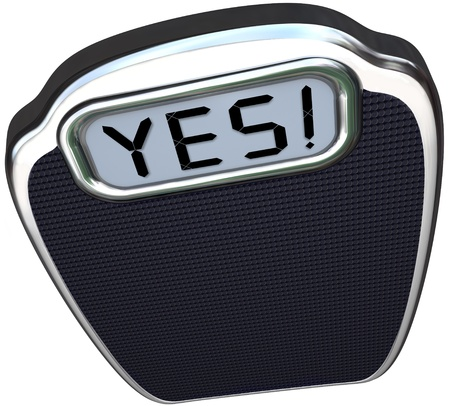 weighing scale: The word Yes on the digital display of a scale to give you positive results after diet or weight loss plan that has proven successful