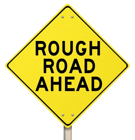 rough road: A yellow diamond-shaped road sign cautions people that rough roads are ahead