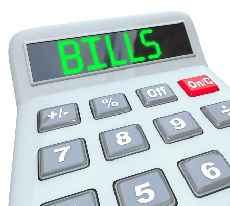mortgaging: A plastic calculator showing the word Bills representing time to pay off your expenses with payments to your mortgage company, utilities and other regular or monthly bill invoices to pay Stock Photo