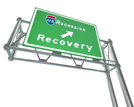 A green freeway sign against white background with the words US Recession - Recovery Stock Photo - 17800984