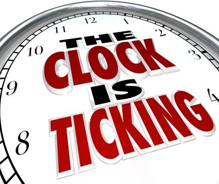 startpunt: Een witte klok met de woorden The Clock is Ticking om een dreigende deadline of einde symboliseren om een gebeurtenis of periode Stockfoto