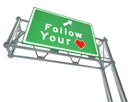 love words: Follow Your Heart to future of success, dreams and growth.  Thats the message of this freeway sign with an arrow pointing to a path that takes you where you want to go Stock Photo