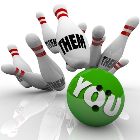 succeeding: The word You on a green bowling ball striking many pins with the words Them to symbolize your chance at winning the game or succeeding against your competition