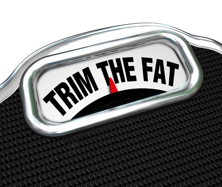 low calorie: The words Trim the Fat on a scale, representing the need to diet and lose weight or to tighten your budget and cut costs during tough economic or financial times Stock Photo