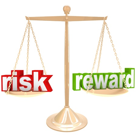 heavy risk: Weighing the risks and rewards of a situation or issue on a gold metal scale, one word on each side, comparing the positives and negatives Stock Photo