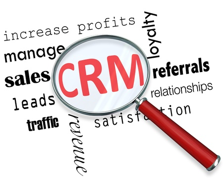 focuses: A magnifying glass hovering over several sales related words and focuses on CRM - which stands for customer relationship management Stock Photo