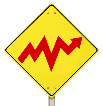 A yellow diamond-shaped road sign with an arrow going up and down in a volatile fashion representing bipolar nature of stock market and the economy, or the emotional rise and fall of bipolar disorder