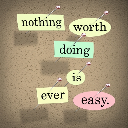 surmount: The quote or saying words Nothing Worth Doing is Ever Easy in pieces of paper pinned to a bulletin board to motivate or inspire you to succeed Stock Photo