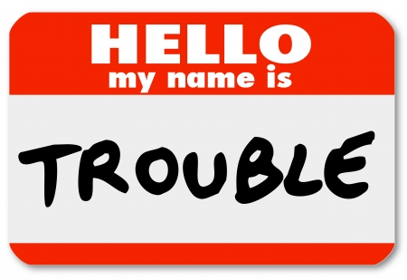 name tags: A namtag sticker with the words Hello My Name is Trouble representing a problem, issue, annoyance, mischief, danger, pain or stress Stock Photo