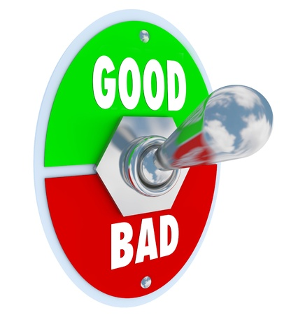 The words Good and Evil on a toggle switch lever to decide or judge whether something is beneficial or harmful to you in life, career or business Stockfoto