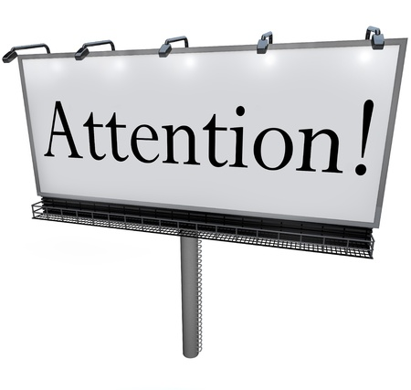 The word Attention on a big outdoor advertisement billboard to communicate a special announcement or urgent message to the public or customers photo