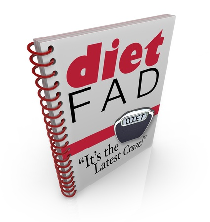 A spiral-bound book with the words Diet Fad - Its the Latest Craze to illustrate a new dieting sensation inside a best-selling manual or guide to help you lose weight Stock Photo