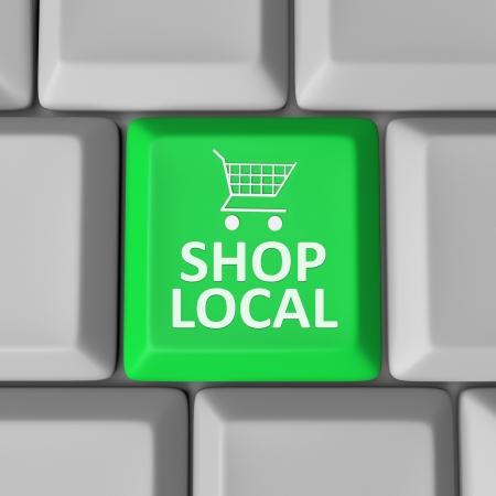 Een groene sleutel van de computer met de woorden Shop Local en een winkelwagentje te moedigen u aan om uw gemeenschap te steunen door het uitgeven van geld in je eigen stad