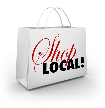 buy local: The words Shop Local on a white shopping bag encouraging you to support your local community or hometown by buying merchandise in your backyard and keeping money nearby