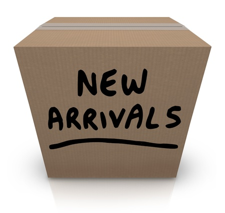 The words New Arrivals written on a cardboard box full of the latest and newest products and merchandise delivered to the store, the seller, or to you, the buyer photo