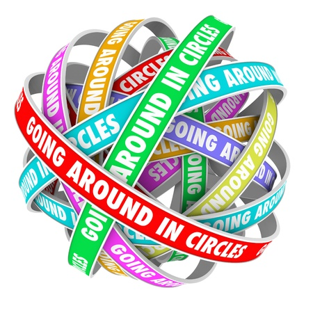 stuck: The words Going Around in Circles on colorful ribbons stuck in an endless repetitive circular pattern to illustrate being lost or confused Stock Photo