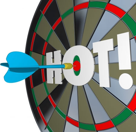 A dart hits the center of a bulls-eye with the word Hot to illustrate a great job or perfomance and top popularity level or buzz Stock Photo - 19587136
