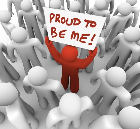 standout: One unique or different person holds a sign in a crowd with the words Proud to Be Me to illustrate standing out in a group of people
