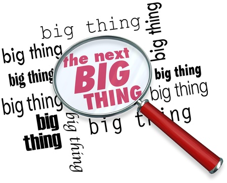 newest: A magnifying glass on the words The Next Big Thing to illustrate finding the latest or newest trend, craze, style, fad or fashion that is popular with the public