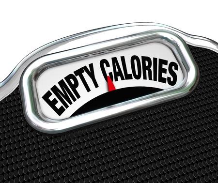 Las palabras calorías vacías en la pantalla de una escala para ilustrar la importancia de comer alimentos nutritivos para una buena salud en lugar de chatarra o comida rápida tales como aperitivos, dulces u otros artículos azucarados Foto de archivo - 20323649
