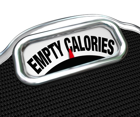 intake: The words Empty Calories on the display of a scale to illustrate the importance of eating nutritional foods for good health instead of junk or fast food such as snacks, candy or other sugary items Stock Photo