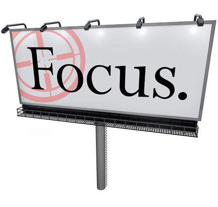reticle: A large white billboard with the word Focus and a target reticle to illusstrate the importance of focusing, aiming or concentrating on your goal or mission in life, work, education or career