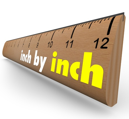 inch: The words Inch by Inch on a wooden ruler to measure your incremental growth, increase or length